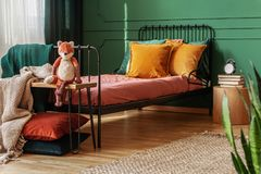 Close-up of a frame bed for a child with orange pillows standing against green wall in bright bedroom interior. Real photo royalty free stock image