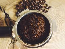 Close up of metal portafilter filled with coffee powder and coffee beans around on wooden table stock photo