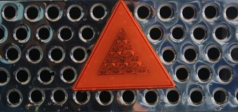Close up of a metal shiny grid with an orange light reflecting warning triangle stock image