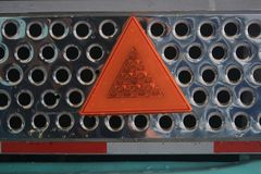 Close up of a metal shiny grid with a orange light reflecting warning triangle and a red-white line stock photo