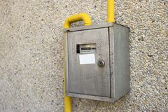 Close-up of metal steel gas meter box with connecting yellow pip. Es hanging on exterior light stone house wall. Construction, renovation, measurement tool and royalty free stock images