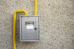Close-up of metal steel gas meter box with connecting yellow pip. Es hanging on exterior light stone house wall. Construction, renovation, measurement tool and stock image