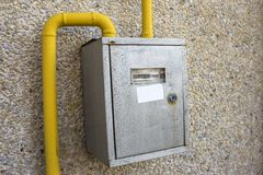 Close-up of metal steel gas meter box with connecting yellow pipes hanging on exterior light stone house wall. Construction, royalty free stock photos