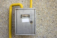 Close-up of metal steel gas meter box with connecting yellow pipes hanging on exterior light stone house wall. Construction,. Renovation, measurement tool and royalty free stock photo