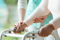 Close-up of metal walker. Close-up photo of patient`s hands placed on metal walker Stock Images