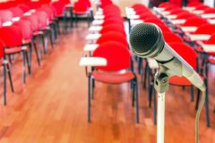Close up of microphone in conference room. Close up of microphone in front of empty chairs in conference room royalty free stock images