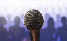 Close up of microphone in front of a silhouette audience. Close up of microphone in front of a silhouette audience and crowd of people. Public speaking and royalty free stock photo