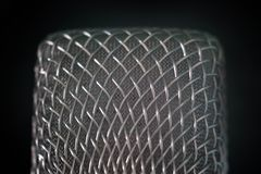 Close-up of the microphone grille of steel wire on a black background. Macro shooting with shallow depth of field. The concept of. Close-up of the microphone stock photos