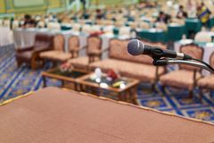 Close up microphone have participant in conference room as background. Close up microphone on table have blur vip seats and participant in conference room as Stock Photos