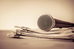 Close up a Microphone with paper document , concept of speaker o. Close up Microphone with paper document , concept of speaker or teacher preparation to speak in stock photo
