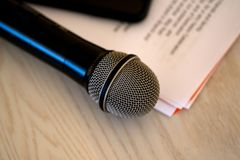 Close up microphone with paper notecards. Concept of speaker preparation to speak. Wedding speech stock photography