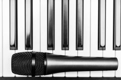 Close up microphone on piano keyboard in music studio. Royalty Free Stock Photography