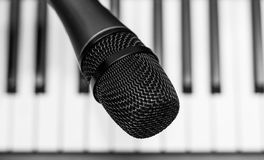 Close up microphone on piano keyboard in music studio. Royalty Free Stock Photo