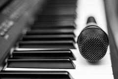 Close up microphone on piano keyboard in music studio. Royalty Free Stock Image