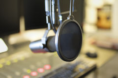 Close-up of a microphone in radio station broadcasting studio. Close-up of a microphone in front of the sound mixer and computers in broadcasting radio studio stock photography