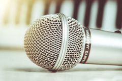 Close up on a microphone during recording session with a singer, piano in the background, music studio. royalty free stock images