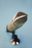 Close up of microphone at recording studio. Technology, electronics and audio equipment concept - close up of microphone at recording studio or radio station Royalty Free Stock Photos