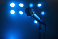 Close-Up Microphone Shot. A close up view of a microphone and stand.  The background is blue and has several spotlights. Horizontally framed shot Royalty Free Stock Photos