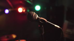 Close-up of microphone on stage in the dark on a color light background. Slow motion.  stock video footage
