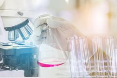 Close up microscope equipment for research experiments with scientist hand holding flask with  liquid and glass test tubes Stock Photo