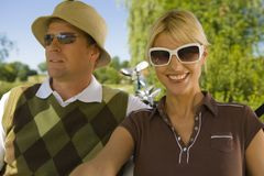Close-up of a mid adult couple sitting in a golf cart and smiling.  stock photos