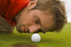 Close-up of a mid adult man judging a golf ball. Close-up of a mid adult man judging a golf ball on a golf course Royalty Free Stock Photos