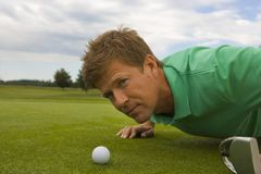 Close-up of a mid adult man judging a golf ball on a golf course.  Royalty Free Stock Images