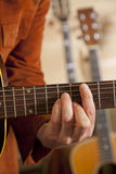 Close-up of mid adult man's fingers while playing guitar Royalty Free Stock Images