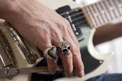Close-up of mid adult man's fingers with rings playing guitar Stock Images