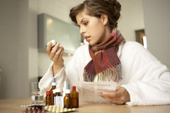 Close-up of a mid adult woman checking medicines with their bill Stock Images