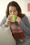 Close-up of a mid adult woman drinking a cup of tea. Wearing a scarf indoors Royalty Free Stock Images