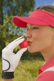 Close-up of a mid adult woman kissing a golf ball. Close-up of a mid adult woman wearing a red cap kissing a golf ball Stock Photography