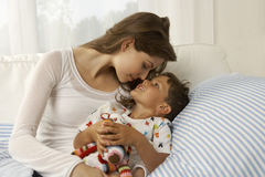 Close-up of a mid adult woman playing with her son on the bed Royalty Free Stock Photo