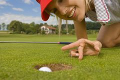 Close-up of a mid adult woman putting a golf ball into a hole.  Stock Photography