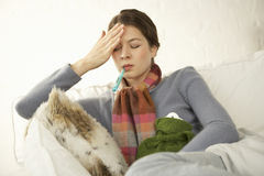 Close-up of a mid adult woman sitting on the bed and measuring her temperature Royalty Free Stock Photo