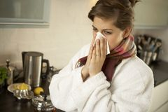 Close-up of a mid adult woman sneezing. Royalty Free Stock Photography