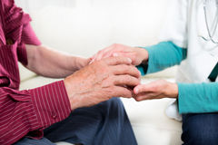 Close-up mid section of a doctor holding patients hands Stock Images