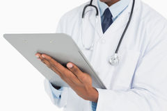 Close up mid section of a male doctor writing on clipboard Stock Photography
