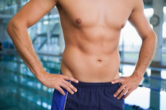 Close up mid section of a shirtless fit swimmer by pool. Close up mid section of a shirtless fit swimmer by the pool at leisure center Royalty Free Stock Images