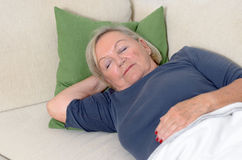Close up Middle Aged Blond Woman Resting on Couch Royalty Free Stock Images