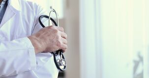 Close up middle aged male doctor holding stethoscope in hands.