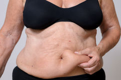 Close up Middle Aged Woman Holding her Fatty Belly Stock Photos