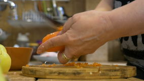 Close-up of middle aged woman peeling a carrot at home in kitchen using traditional recipe for a healthy meal stock video