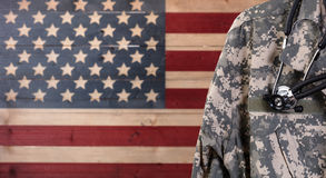 Close up of military uniform jacket and stethoscope with rustic. Closeup of military uniform with stethoscope against faded boards painted in USA flag background stock photo