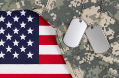 Close up of military uniform on USA Flag. Flag of the United States of America with military identification tags, neck chain, and combat uniform top. Military stock photos