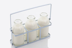 Close up of milk bottles in rack on white background Stock Image