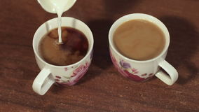 Close-up of milk pouring into the two coffee Cup. stock video footage