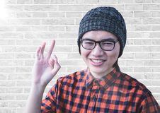 Close up of millennial man making ok sign with flare against white brick wall. Digital composite of Close up of millennial man making ok sign with flare against Royalty Free Stock Photo