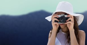 Close up of millennial woman in summer hat with camera against blurry mountain. Digital composite of Close up of millennial woman in summer hat with camera Stock Photo