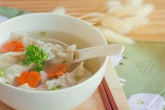 Close up minced pork wonton soup in white bowl on wood cutting b royalty free stock photography